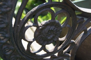 A decorative iron piece on an old bench, every part of it curves in some way