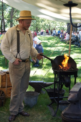 One of the smiths would keep the forge hot by manually pumping the mechanical bellows.