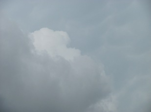 A break in the lower clouds revealed a portion of towering cumulus above